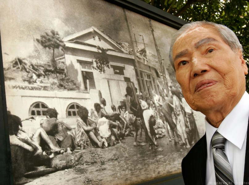 SUNAO TSUBOI: A-Bomb survivor, standing in front of one of the few pictures taken in the first days of the bombing and in which he can recognize himself between the wounded.